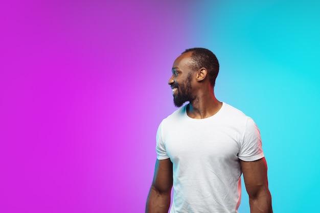 Uśmiechnięty portret młodego afroamerykańskiego mężczyzny na gradientowym tle studyjnym w neonowym