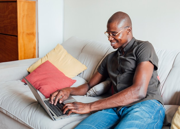 Uśmiechnięty portret młodego człowieka obsiadanie na kanapie używać laptop