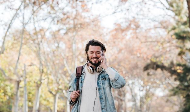 Uśmiechnięty portret młodego człowieka odprowadzenie z jego plecakiem opowiada na telefonie komórkowym w parku