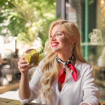 Uśmiechnięty portret młodej kobiety mienia słodka bułeczka w ręce patrzeje daleko od