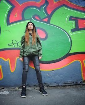 Uśmiechnięty portret młodej kobiety z dredami, przeciw graffiti