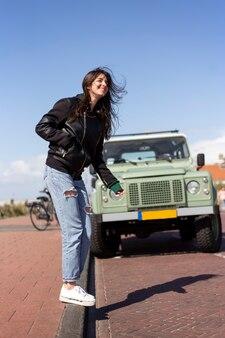 Uśmiechnięty portret młodej kobiety z włosami wiejący wiatr. ona ma na sobie skórzaną kurtkę z samochodem i drogą w tle.