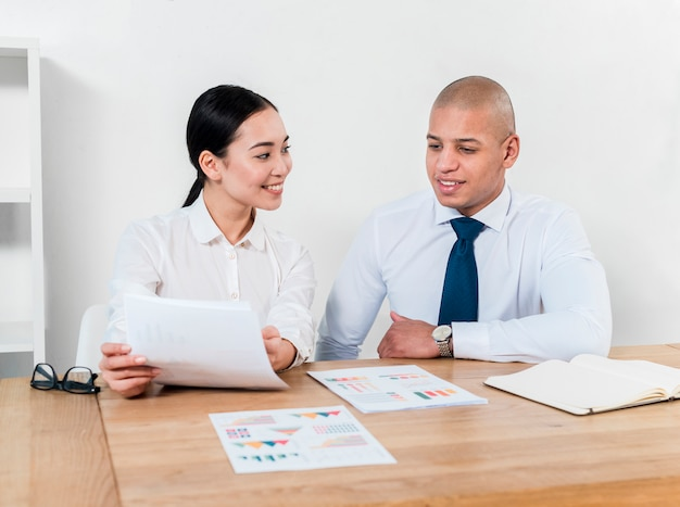Uśmiechnięty portret młody biznesmen i bizneswoman dyskutuje raport przy miejscem pracy