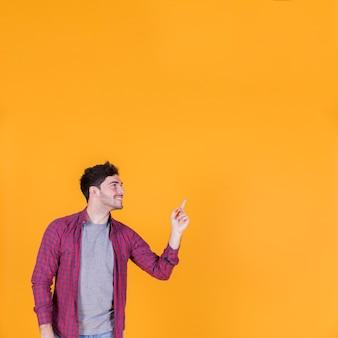 Uśmiechnięty portret młody człowiek pokazuje coś na pomarańczowym tle