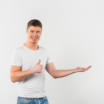 Uśmiechnięty portret młody człowiek pokazuje kciuk up podpisuje przedstawiać przeciw białemu tłu
