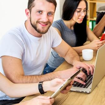 Uśmiechnięty portret młody człowiek pracuje na laptopie nad drewnianym biurkiem