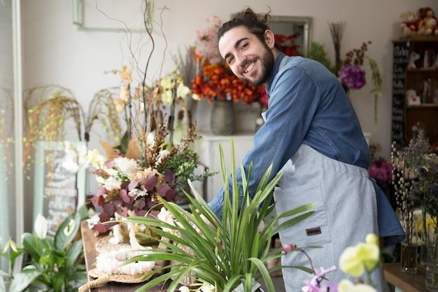Uśmiechnięty portret młody człowiek układa kwiatu w kwiaciarnia sklepie
