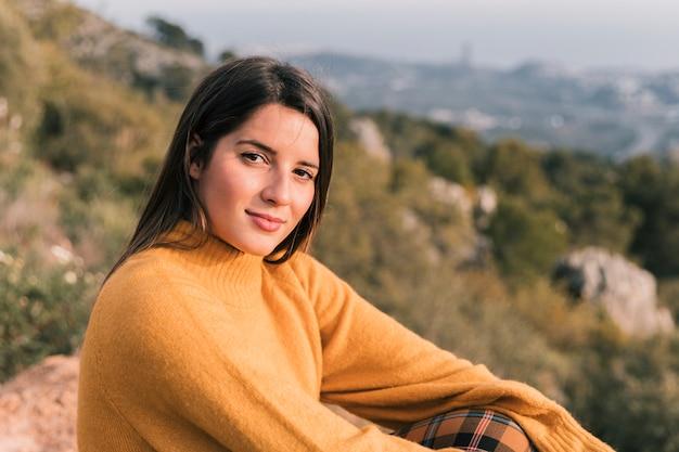 Uśmiechnięty portret młody żeński wycieczkowicz siedzi na halnym wierzchołku patrzeje kamerę