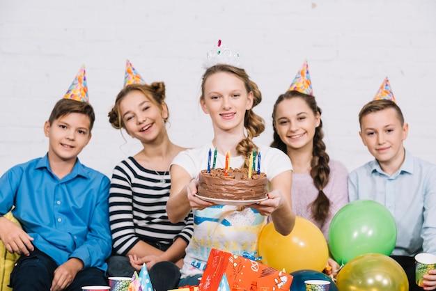 Uśmiechnięty portret nastoletniej dziewczyny obsiadanie z jej przyjaciółmi trzyma urodzinowego tort