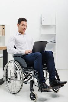 Uśmiechnięty portret niepełnosprawnego młodego człowieka siedzi na wózku inwalidzkim przy użyciu laptopa w miejscu pracy