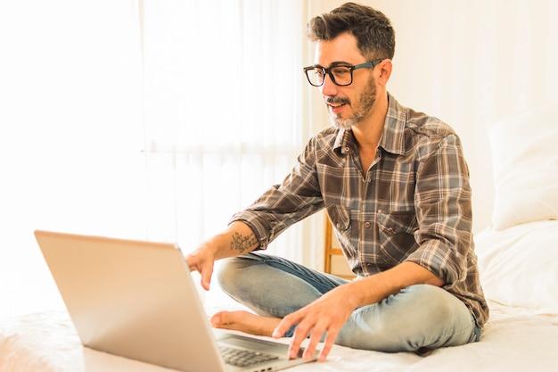 Uśmiechnięty portret nowożytny mężczyzna siedzi na łóżku używać laptop