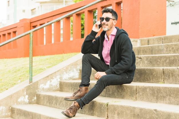 Uśmiechnięty portret nowożytny mężczyzna siedzi na schody opowiada nad telefonem komórkowym