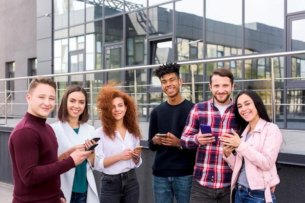 Uśmiechnięty portret rozochoceni młodzi ucznie używa mądrze telefony stoi na zewnątrz budynków