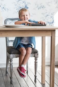 Uśmiechnięty portret śliczny chłopiec obsiadanie przy drewnianym łomota stołem z książką