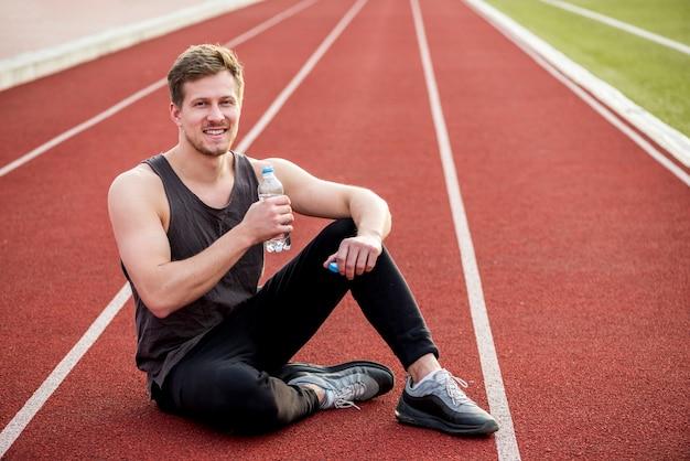Uśmiechnięty portret sportowca siedzi na torze wyścigowym, trzymając w ręku butelkę wody