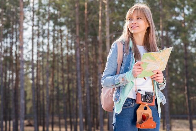 Uśmiechnięty portret żeński wycieczkowicz trzyma mapę w ręce wycieczkuje w lesie