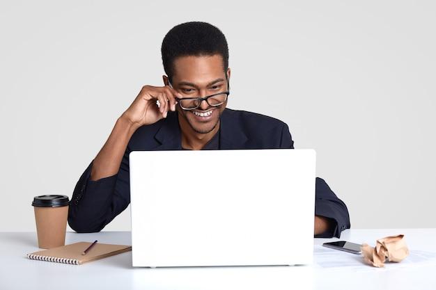 Uśmiechnięty pozytywny ciemnoskóry mężczyzna nosi przezroczyste okulary, skupia się na komputerze przenośnym, robi daleką pracę, zapisuje coś w notatniku, pije kawę na wynos, na białym tle na białej ścianie.