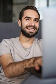 Uśmiechnięty pozytywny młody człowiek pomieszczeniu w domu na kanapie przy użyciu komputera przenośnego.