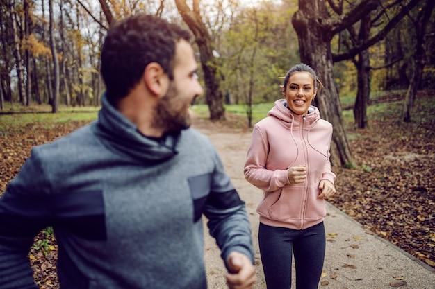 Uśmiechnięty pozytywny młody człowiek w odzieży sportowej ściga się ze swoją dziewczyną i wygrywa. fitness w koncepcji natury.