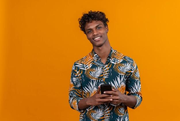 Uśmiechnięty pozytywny młody przystojny ciemnoskóry mężczyzna z kręconymi włosami w liściach drukowanej koszuli trzyma telefon komórkowy, patrząc na kamery na pomarańczowym tle
