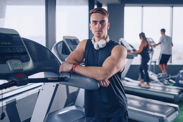 Uśmiechnięty pozytywny, pewny siebie osobisty instruktor mężczyzna z rękami skrzyżowanymi w pobliżu bieżni na siłowni w siłowni fitness