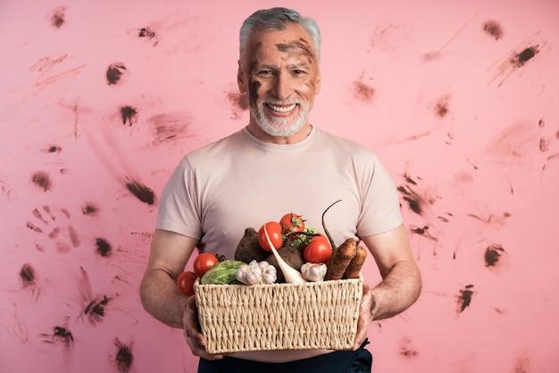 Uśmiechnięty, pozytywny starszy mężczyzna trzyma kosz świeżych warzyw przed brudną różową ścianą