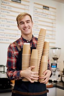 Uśmiechnięty pracownik barista w fartuchu trzymający dużo picia jednorazowych papierowych kubków w kawiarni