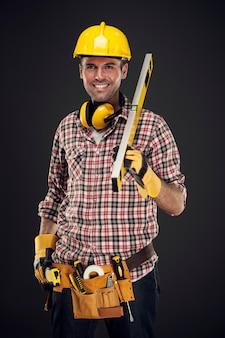 Uśmiechnięty pracownik budowlany mienia mierzenia