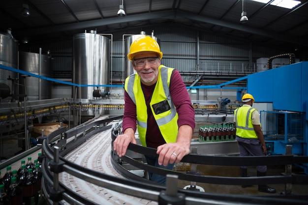 Uśmiechnięty pracownik fabryczny opiera na linii produkcyjnej