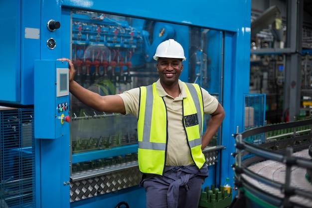Uśmiechnięty pracownik fabryczny stoi blisko maszynowego kontrolnego gabineta