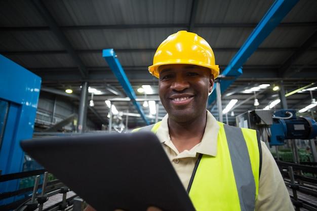 Uśmiechnięty pracownik fabryczny używa cyfrową pastylkę w fabryce