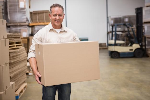 Uśmiechnięty pracownik niesie pudełko