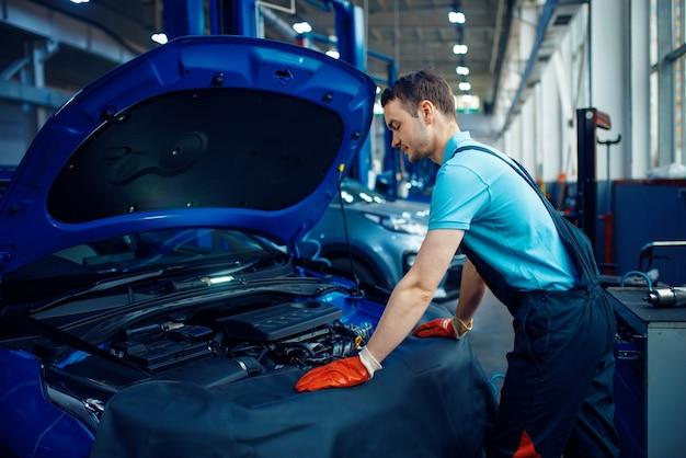 Uśmiechnięty pracownik płci męskiej w mundurze sprawdza silnik pojazdu, stacja obsługi samochodów. sprawdzenie i przeglądy samochodów, profesjonalna diagnostyka i naprawa