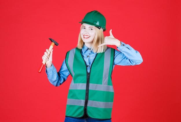 Uśmiechnięty pracownik płci żeńskiej trzymaj młotek i wykonywania gestu połączenia z palcem odizolowanym na czerwono