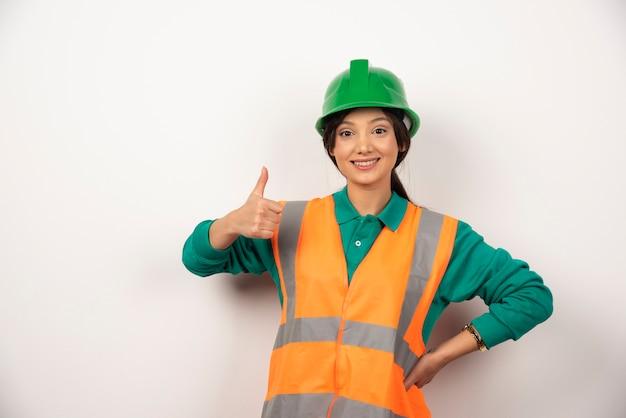 Uśmiechnięty pracownik płci żeńskiej z kciukiem do góry na białym tle.