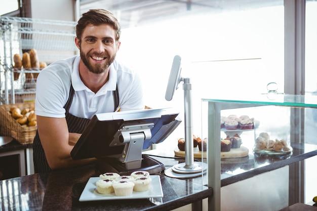Uśmiechnięty pracownik pozuje za kontuarem