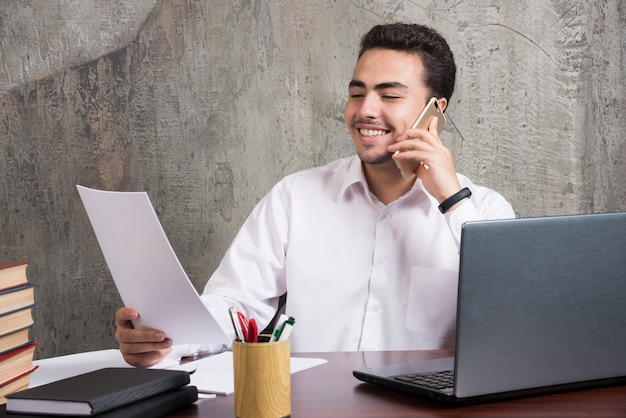 Uśmiechnięty pracownik rozmawia przez komórkę i trzyma kartki papieru. wysokiej jakości zdjęcie