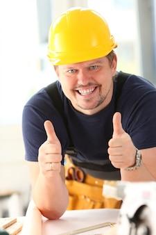 Uśmiechnięty pracownik w żółtym hełmie