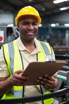 Uśmiechnięty pracownika fabrycznego mienia schowek w fabryce