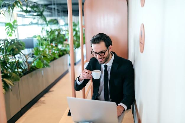 Uśmiechnięty prawnik odnoszący sukcesy w oficjalnym stroju, piszący e-mail i pijący espresso, siedząc przy stole.