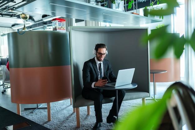 Uśmiechnięty prawnik przygotowuje się do połączenia konferencyjnego i siedzi w stacji roboczej. słuchawki na uszach.