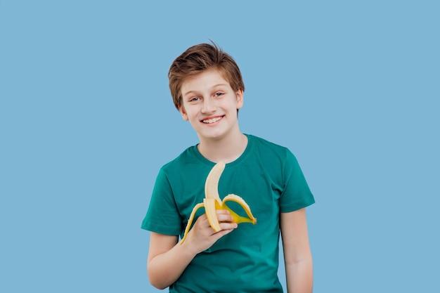Uśmiechnięty preteen chłopiec z bananem w dłoni w zielonej koszulce
