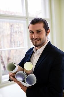 Uśmiechnięty projektant wnętrz trzyma projekty