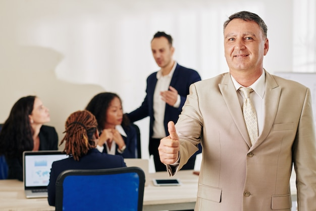 Uśmiechnięty przedsiębiorca pokazuje kciuki do góry