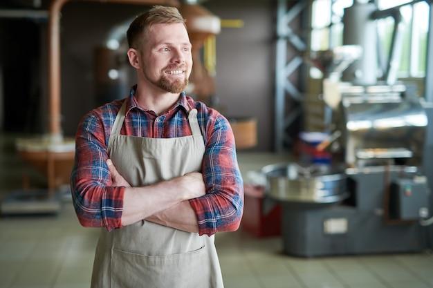 Uśmiechnięty przedsiębiorca pozuje w palarni kawy