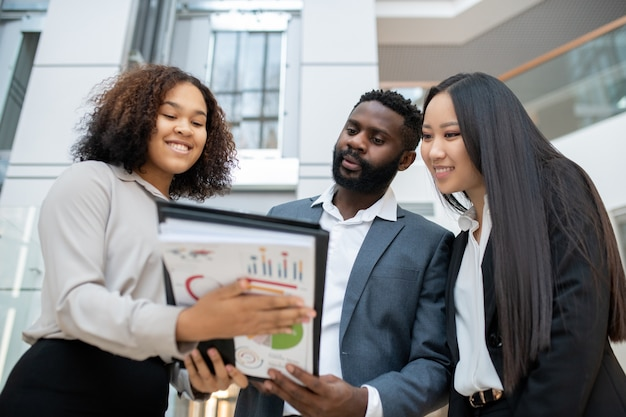 Uśmiechnięty przyjazny czarny doradca finansowy pomaga młodej pary biznesowej z analizą budżetu