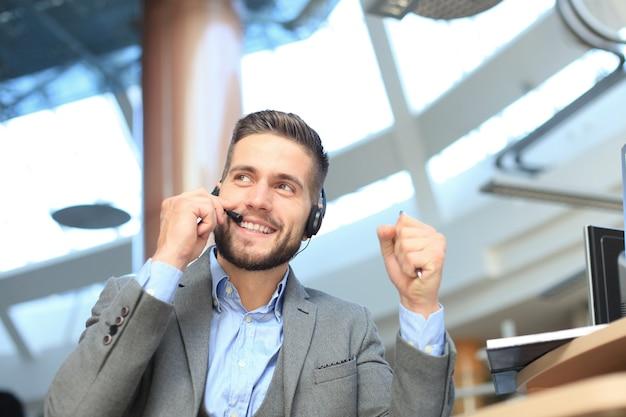 Uśmiechnięty przyjazny przystojny młody mężczyzna call center operatora.
