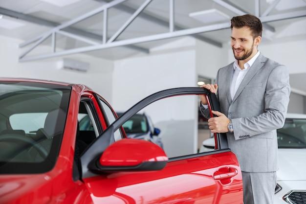 Uśmiechnięty przyjazny sprzedawca samochodów otwierający drzwi na nowy model samochodu