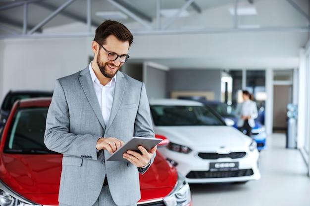 Uśmiechnięty, przyjazny sprzedawca samochodów stojący w salonie samochodowym i za pomocą tabletu sprawdza nowe wiadomości, które klienci umieszczają w internecie