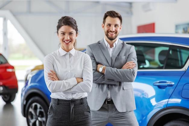 Uśmiechnięty przyjazny sprzedawca samochodów stojący w salonie samochodowym z rękami skrzyżowanymi. dla obu stron zawsze przyjemność kupić samochód we właściwym miejscu.